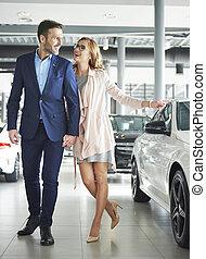 Couple choosing certain car in the showroom