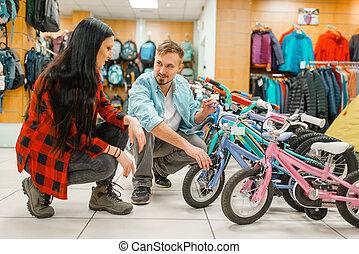 Couple choosing children's bicycle, shopping