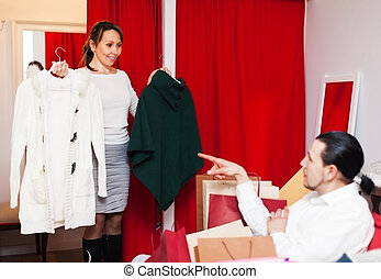 Couple choosing coat in fitting-room at store