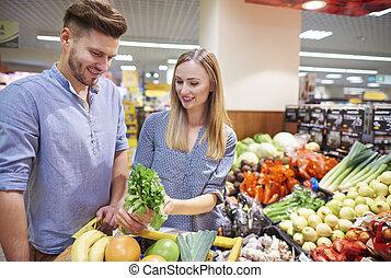Couple choosing fresh food in supermarket