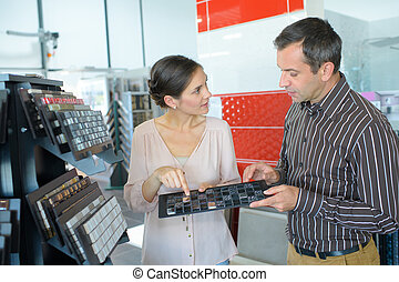 couple choosing from colorful tile samples