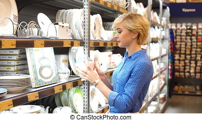 Couple choosing household goods in retailer. Consumerism,...