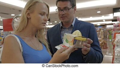 Couple choosing juicer in the supermarket