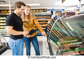 Couple Choosing Meat From Display Cabinet