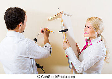 Couple choosing place for shelf