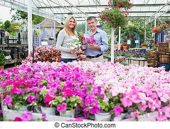 Couple choosing plants in the garden centre