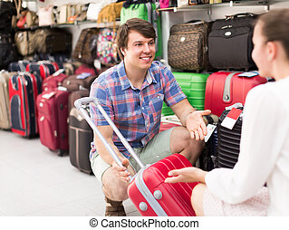 Couple choosing suitcase in shop