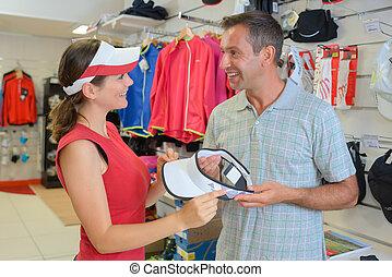 Couple choosing sun visor in sports shop