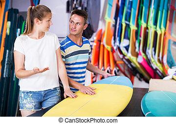 Couple choosing surfboard