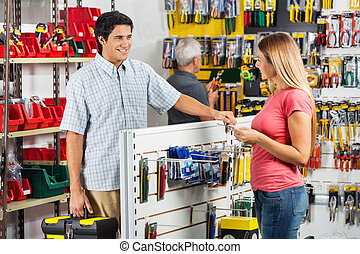 Couple Choosing Tools In Hardware Store