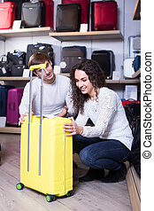 Couple choosing travel suitcase in shop.