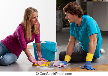 A couple cleaning the floor with dusters and lather