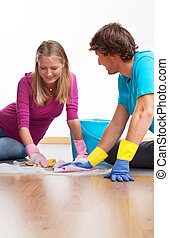 Couple cleaning the floor