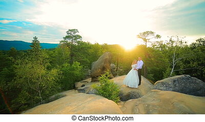 Couple climbing on the rock and admiring the sunrise, the...