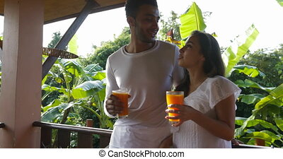 Couple Clinking Juice Glass Talking On Balcony, Man And...