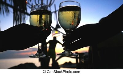 Couple clinks glasses of wine in beach cafe after sunset....