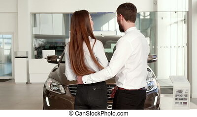 Couple comes closer to the black car at the dealership