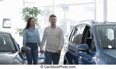 Couple comes to the blue SUV at the dealership