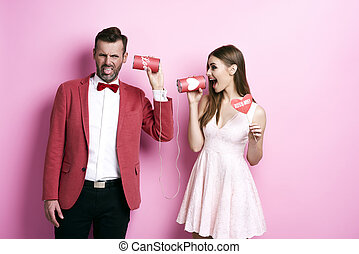 Couple communicating on tin can phone