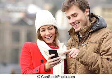 Couple consulting a smart phone in winter