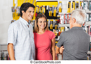 Couple Conversing With Man In Hardware Store