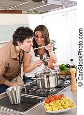 Couple cook in modern kitchen - man taste food