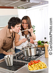 Couple cook in kitchen - man taste food - Couple cook in...