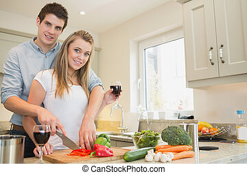 Couple cooking and drinking wine