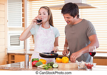 Couple cooking dinner while drinking wine
