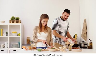 couple cooking food and drinking wine at home - people and...