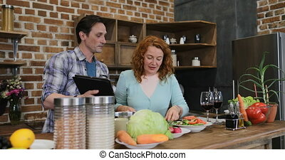 Couple Cooking In Kitchen Together Using Recipe From Tablet Digital Computer, Man And Woman Preparing Food At Home