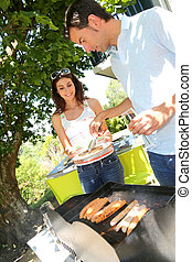 Couple cooking meat on barbecue grill