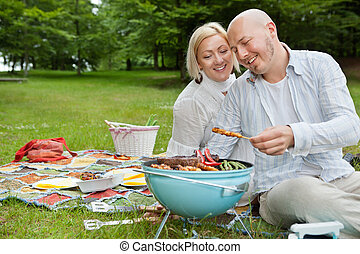 Couple Cooking Meat On Barbecue - Happy mature couple...