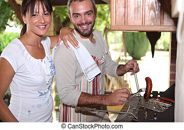 Couple cooking sausages on the barbecue