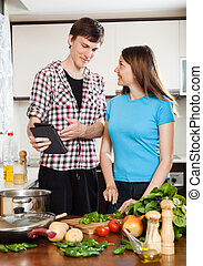 couple cooking with eBook