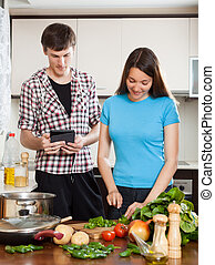 Couple cooking with electronic Book