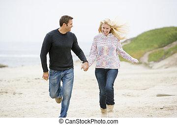 couple, courant, à, plage, tenant mains, sourire