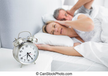 Couple covering their ears from alarm clock noise