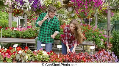 Couple coworking in blooming garden - Young man having phone...