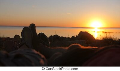 Couple cuddling with feet at sunset in tent