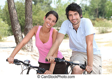 Couple cycling through a coastal pine forest
