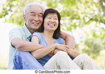 couple, délassant, dehors, dans parc, sourire