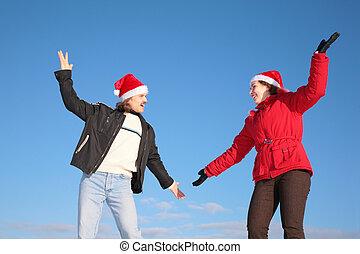 couple dance in santa claus hats against blue sky