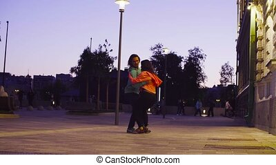 Couple dancing in the city near the building