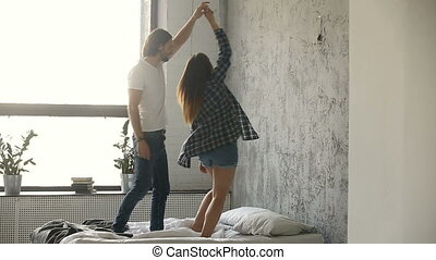 Couple dancing on bed, woman spinning around holding...