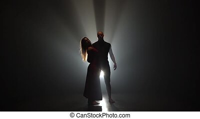 Couple dancing on the background of a spotlight in a dark studio. Slow motion