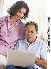 couple, dans, salle de séjour, à, ordinateur portable