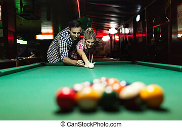 Couple dating and having fun playing snooker