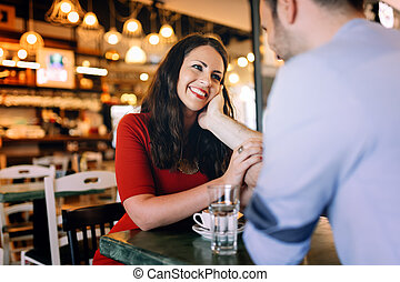 Couple dating in restaurant while drinking coffee