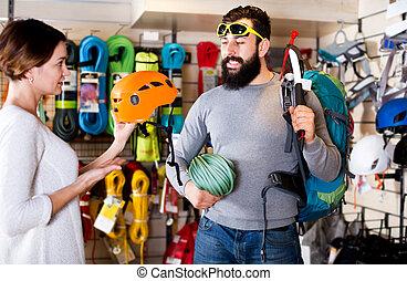 Couple deciding on climbing equipment